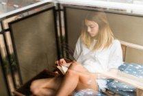 Mujer leyendo un libro en el balcón - foto de stock