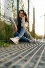 Donna posa a terra vicino alla recinzione — Foto stock