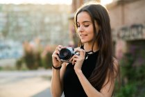 Pretty woman setting a camera — Stock Photo