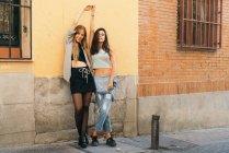 Teen amiche in posa con le braccia alzate — Foto stock