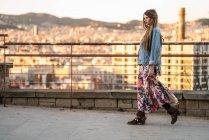Mujer caminando contra la ciudad - foto de stock