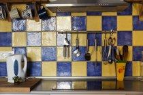 A superfície de trabalho com fogão elétrico e talheres na cozinha — Fotografia de Stock