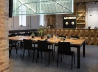Tourné à l'intérieur de la cafétéria vide avec grande table entourée de chaises. — Photo de stock