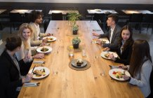 Group of young coworkers having dinner together sitting at big table in spacious light canteen. — Stock Photo