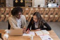 Colleghi che si siede sul desktop con il computer portatile e lavorano insieme al documento. — Foto stock