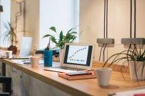Ноутбук с диаграммами на деревянном столе — стоковое фото
