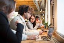 Seitenansicht der junge Büroangestellte am Schreibtisch sitzen und arbeiten in modernen Büros mit laptop — Stockfoto