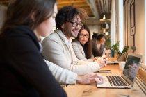 Mitarbeiter am Schreibtisch sitzen und beobachtete Laptop während der Diskussion im modernen Büro — Stockfoto