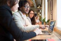Mitarbeiter am Schreibtisch sitzen und beobachtete Laptop im modernen Büro. — Stockfoto