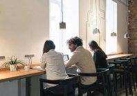 Vista posteriore di gente seduta vicino alla finestra nel desktop e avere conversazione in ufficio. — Foto stock
