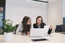 Two female colleagues working with papers and laptop — Stock Photo