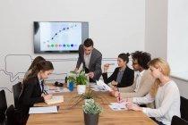 Gruppo di giovani che si siede al tavolo e utilizzo di diagrammi in ufficio. — Foto stock