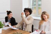 Drei Kollegen lachen während der Arbeit an Diagrammen im Büro — Stockfoto