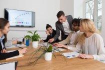 Группа коллег, сидя за столом и обсуждении диаграммы вместе в отделение света — стоковое фото