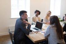Молодые коллеги на совещании в современном офисе — стоковое фото