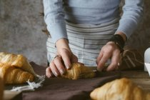 Female hands slicing croissant — Stock Photo
