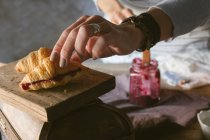 Female hands closing sliced croissant with jam — Stock Photo