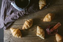 Croisants with cup on wooden table — Stock Photo