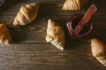 Croisants with jar of jam on wooden table — Stock Photo