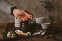 Mani che tengono cucchiaio in tazza — Foto stock