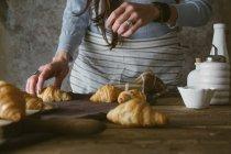 Female hands taking croissant — Stock Photo