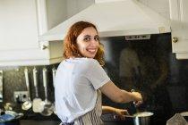 Mujer sonriente cocinar en casa - foto de stock