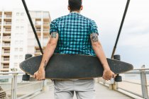 Man with tattoos holding skateboard — Stock Photo