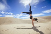 Woman in handstand on sands — Stock Photo