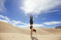 Woman practicing yoga in sands — Stock Photo