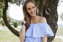 Chica bastante joven sonriendo en la naturaleza - foto de stock