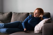Woman on couch surfing channels — Stock Photo