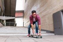 Guapo patinador montar en la calle - foto de stock