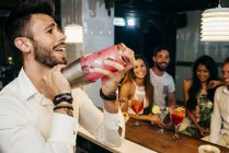 People watching bartender in bar — Stock Photo