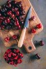 Cerezas en una tabla para cortar madera - foto de stock