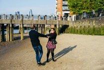 Couple spinning on beach — Stock Photo