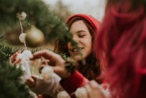 Portrait of two girls decorating fir tree with garland for Christmas — Stock Photo