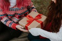 Mid section of girl giving gift with red ribbon to friend while sitting on ground in forest — Stock Photo