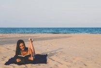 Женщина читает книгу на пляже — стоковое фото