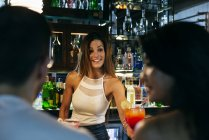 Smiling woman bartender giving cocktail — Stock Photo