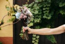 Hand mit Blumenstrauß — Stockfoto