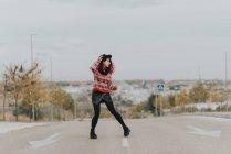 Muchacha con sombrero posando en carretera urbana - foto de stock