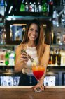 Female bartender serving cocktail — Stock Photo