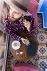 Hombre en sombrero con teléfono y café - foto de stock