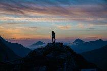 Silhouette de fille debout sur le sommet de la montagne sur fond de ciel de coucher de soleil brumeux — Photo de stock