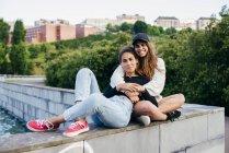 Encantadores amigos abrazando fuera - foto de stock