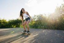 Teen riding skateboard in sunlight — Stock Photo