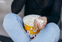 Crop girl with popcorn in hand — Stock Photo