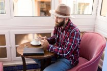 Male in hat using phone — Stock Photo