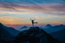 Silhouette of tourist cheering sunset on mountain top against of amazing sky — Stock Photo