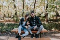 Улыбаясь пара, сидя на столе парк и просмотра смартфон — стоковое фото